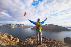 Travel to Norway, happy tourist hiker with flag. Travel to Norway, happy tourist hiker with backpack standing on the top of mountain and holding norwegian flag stock images