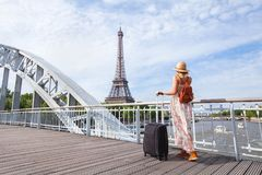 Travel to Paris, Europe tour, woman with suitcase near Eiffel Tower. France Stock Photo