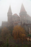 Travel to Romania: Corvin Misty Castle. One of Romanias landmarks, Hunyadi castle shines through the fog. Looks like a witches castle royalty free stock images