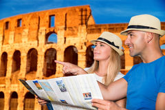 Travel to Rome. Beautiful active couple with map standing on Coliseum background and looking for right way, travel to Rome and exploring it by themselves, Italy Stock Photos