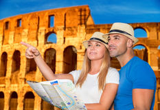 Travel to Rome. Beautiful active couple with map standing on Coliseum background and looking for right way, travel to Rome and exploring it by themself, Italy Stock Photos