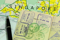 Travel to Singapore. Abstract image of travelling to Singapore with Singapore map, passport with visa stamps and ball pen royalty free stock photography