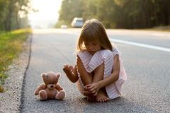 Little girl with Teddy bear on the roadside Stock Photos