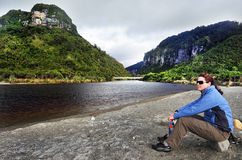Travel to the West Coast of New Zealand. A tourist sits on a west coast beach in southern New Zealand Stock Photos