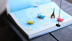 Travel to World idea or Tourism. Paper boats on the map and the Eiffel Tower. stock video footage