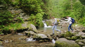 We travel together. A couple of tourists cross the mountain river, a man helps a woman, gives her hand. A young couple of tourists with backpacks crosses a stock video footage