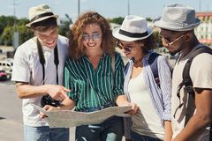 Multiracial friends searching for direction using paper map. Travel together. Multiracial friends searching for direction using paper map stock images