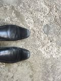 Travel. Top view of Black  Leather Shoes standing on the cement floor , space for text Stock Photos
