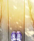 Travel. Top view, concept purple sport shoes on the wooden background, orange light shining from above. space for text Royalty Free Stock Photo