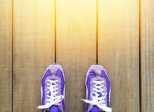Travel. Top view, concept purple sport shoes on the wooden background, orange light shining from above. space for text Royalty Free Stock Photos