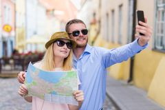 Travel and tourism concept - couple with city map taking photo o Stock Photography