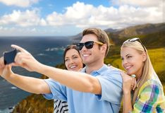 Group of happy friends taking selfie by cell phone. Travel and tourism concept - group of happy friends taking selfie by cell phone over big sur coast of royalty free stock photography