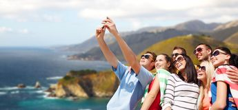 Group of happy friends taking selfie by cell phone. Travel and tourism concept - group of happy friends taking selfie by cell phone over big sur coast of stock images
