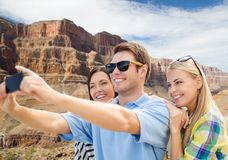 Group of happy friends taking selfie by cell phone. Travel and tourism concept - group of happy friends taking selfie by cell phone over grand canyon national stock photos