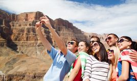 Group of happy friends taking selfie by cell phone. Travel and tourism concept - group of happy friends taking selfie by cell phone over grand canyon national royalty free stock image