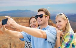 Group of happy friends taking selfie by cell phone. Travel and tourism concept - group of happy friends taking selfie by cell phone over grand canyon national royalty free stock photo