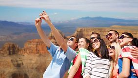 Group of happy friends taking selfie by cell phone. Travel and tourism concept - group of happy friends taking selfie by cell phone over grand canyon national stock images