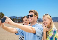 Group of happy friends taking selfie by cell phone. Travel and tourism concept - group of happy friends taking selfie by cell phone over venice beach background stock images