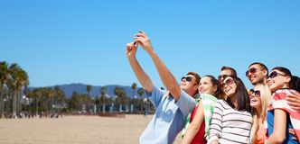 Group of happy friends taking selfie by cell phone. Travel and tourism concept - group of happy friends taking selfie by cell phone over venice beach background stock photography