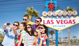 Group of happy friends taking selfie by cell phone. Travel and tourism concept - group of happy friends taking selfie by cell phone over welcome to fabulous las royalty free stock photos