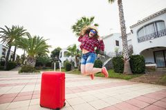 Travel, tourism, emotions and people concept - happy young woman jumped in a hat and sunny glasses near her red suitcase stock photo