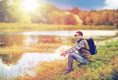 Man with backpack resting on river bank Royalty Free Stock Photo