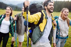 Travel, tourism, hike, gesture and people concept - group of smiling friends with backpacks. Over alpine mountains and hills background stock photo
