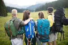 Travel, tourism, hike, gesture and people concept - group of smiling friends with backpacks. Over alpine mountains and hills background royalty free stock photos