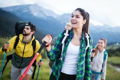 Travel, tourism, hike, gesture and people concept - group of smiling friends with backpacks. Over alpine mountains and hills background royalty free stock images
