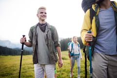 Travel, tourism, hike, gesture and people concept - group of smiling friends with backpacks. Over alpine mountains and hills background royalty free stock image