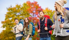 Group of friends with backpacks hiking in autumn. Travel, tourism, hike and people concept - group of smiling friends with backpacks hiking over autumn trees royalty free stock photo