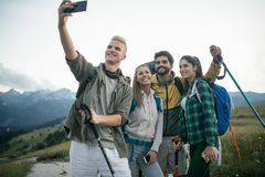 Travel, tourism, hike and people concept - happy group of friends taking selfie and hiking stock photo