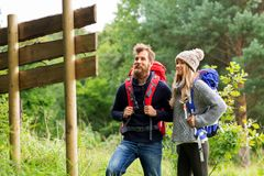 Couple of travelers with backpacks at signpost. Travel, tourism, hiking and people concept - couple of travelers with backpacks looking at signpost stock images