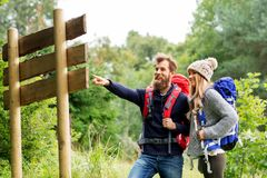 Couple of travelers with backpacks at signpost royalty free stock image