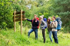 Hiking friends with backpacks at signpost. Travel, tourism, hiking and people concept - group of happy friends or travelers with backpacks looking at signpost stock photos