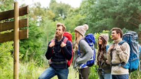 Hiking friends with backpacks at signpost. Travel, tourism, hiking and people concept - group of happy friends or travelers with backpacks looking at signpost royalty free stock images