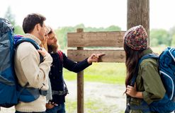 Hiking friends with backpacks at signpost. Travel, tourism, hiking and people concept - group of happy friends or travelers with backpacks looking at signpost royalty free stock image