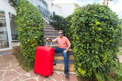 Travel, tourism and holidays concept - happy man sitting on stairs in sunny glasses holding the red suitcase royalty free stock image