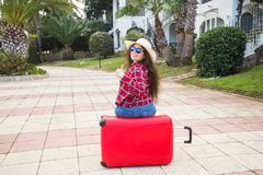 Travel, tourism and holidays concept - happy young woman sitting on red suitcase in glasses and hat showing thumb up and royalty free stock images