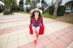 Travel, tourism and holidays concept - happy young woman sitting on red suitcase in glasses and hat and smiling stock photo