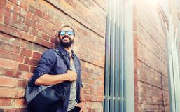 Happy man with backpack standing at city street. Travel, tourism, lifestyle and people concept - happy smiling man with backpack standing at city street wall Royalty Free Stock Image