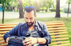 Man with backpack and earphones in city. Travel, tourism, lifestyle and people concept - man with earphones and sunglasses sitting on city bench and looking for Royalty Free Stock Image