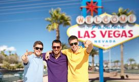 Group of male friends hugging over las vegas sign. Travel, tourism and male friendship concept - group of friends hugging over welcome to fabulous las vegas sign Royalty Free Stock Photography