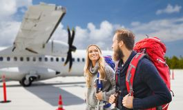 Couple of tourists with backpacks over plane royalty free stock images