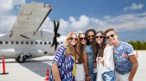 Friends taking picture by selfie stick on airfield royalty free stock photography