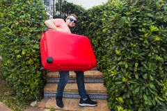 Travel, tourism and people concept - happy man climbing up the stairs with red suitcase and smiling.  royalty free stock images