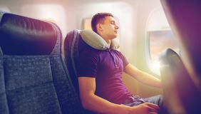 Young man sleeping in plane with travel pillow. Travel, tourism and people concept - happy young man sleeping in plane with inflatable pillow over porthole Stock Image