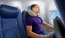 Young man sleeping in plane with travel pillow. Travel, tourism and people concept - happy young man sleeping in plane with inflatable pillow over porthole Royalty Free Stock Photos