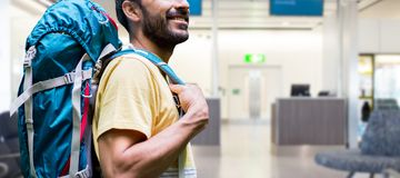 Man with backpack over airport terminal royalty free stock images