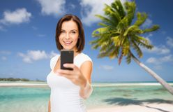 Woman taking selfie by smartphone on beach Royalty Free Stock Photography